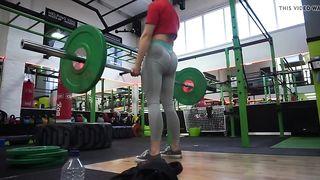 Спортсменка с упругой жопой в лосинах делает становую тягу